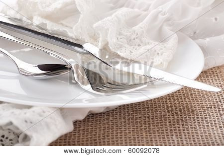 Table fork and knife in a napkin of medieval style, flower