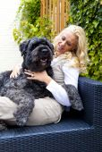 Picture of a young blond woman with her dog - a Bouvier des Flandres, sitting on a garden couch poster