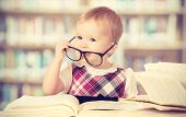 Happy funny baby girl in glasses reading a book in a library poster