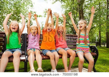 Happy children with arms and sit in row on bench
