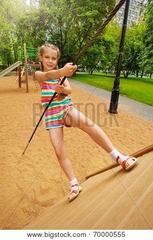 Girl tries to climb on wooden construction