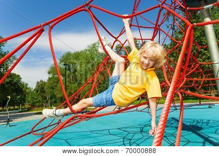 Boy hangs with legs and arms hold the ropes