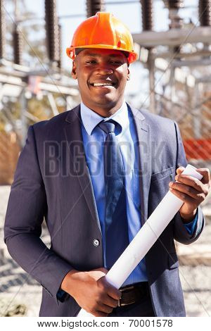 handsome african power company manager standing in electrical substation