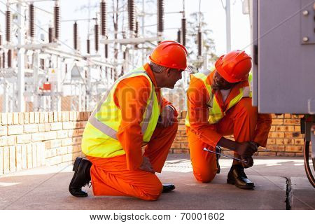 two experienced electricians discussing work in electrical substation