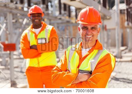 two electricity company workers in substation