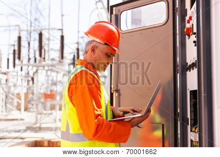 professional mature electrician working on laptop computer in substation
