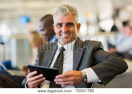 portrait of happy businessman holding tablet computer at airport