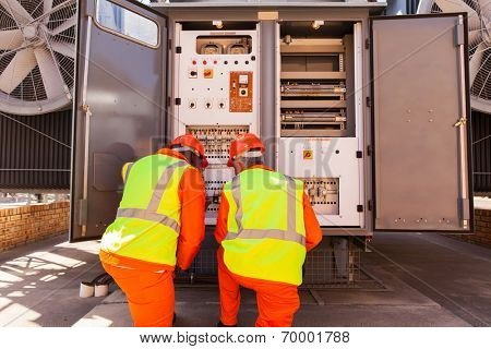 male electricians repairing transformer in substation