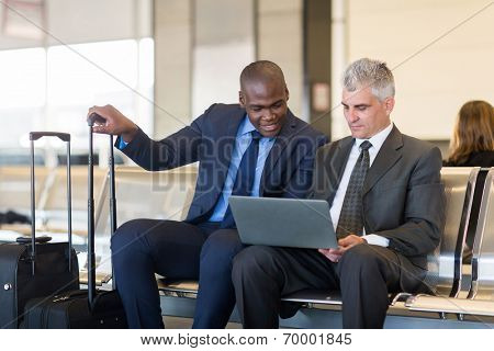 two businessmen working on laptop computer at airport