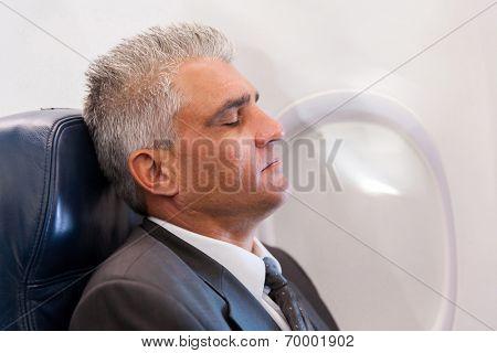 peaceful senior businessman resting on airplane