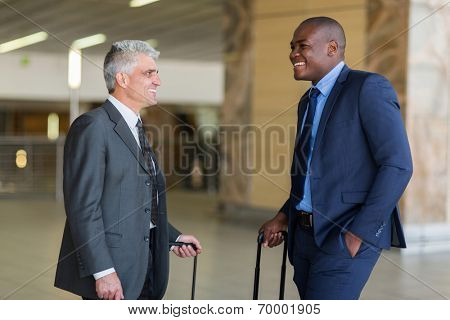 two friendly businessmen talking at airport