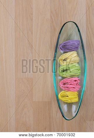 Colourful dried noodles in glass tray