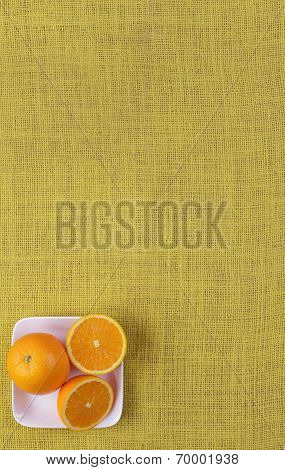 oranges in a white dish on yellow cloth background