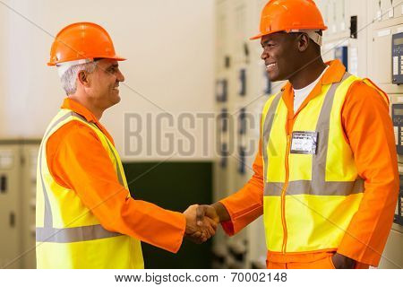 friendly electrical engineers handshaking in power plant control room