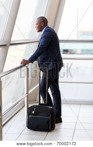 formal young african businessman with luggage at airport