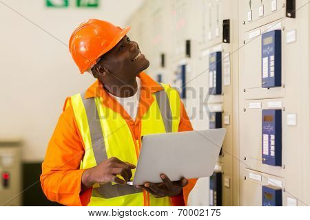 smiling african male industrial engineer using laptop in control room