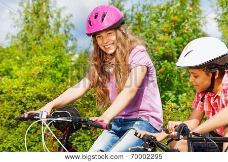Smiling girl in helmet and African boy on bikes