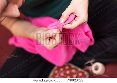 Woman With Needle And Thread