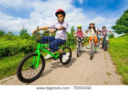 African guy rides bike with friends riding behind