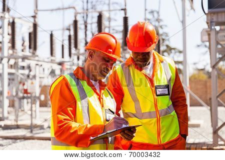 professional senior technician and electrical engineer writing on clipboard in substation