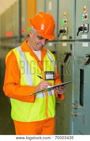 senior industrial technician taking machine readings in control room