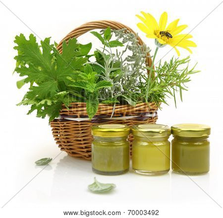 Fresh herbs in wicker basket and cosmetic creams