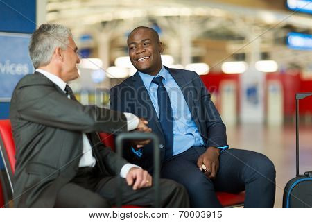friendly business travellers handshaking at airport