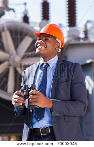 happy african american electrical businessman with binoculars at plant
