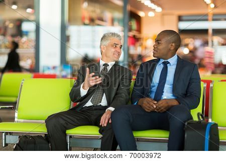 well dressed businessmen waiting for their flight at airport