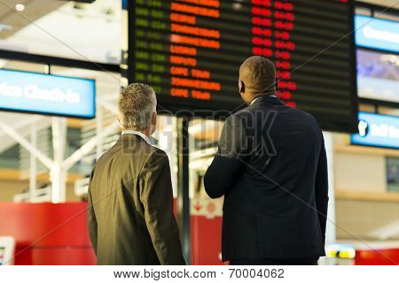 two businessmen looking at flight information board in airport