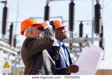middle aged engineer and colleague with binoculars on electrical substation