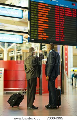 rear view of business partners checking flight information at airport