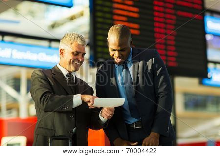 happy business travellers looking at air ticket in airport