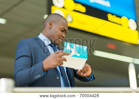 professional african american business traveller checking time at airport