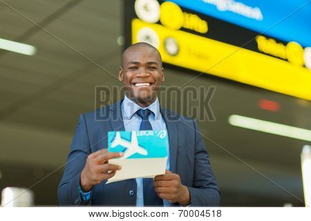 handsome african businessman holding air ticket at airport