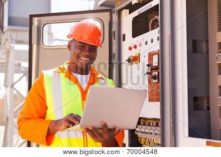 portrait of happy young african electrical engineer with laptop