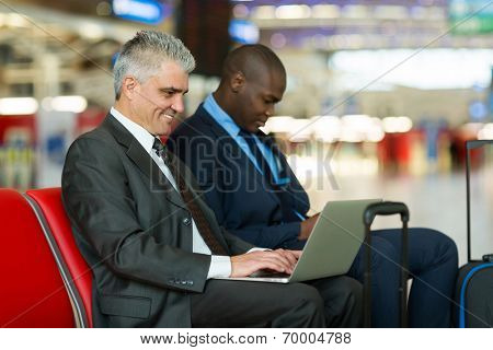 smiling middle aged businessman using laptop computer at airport