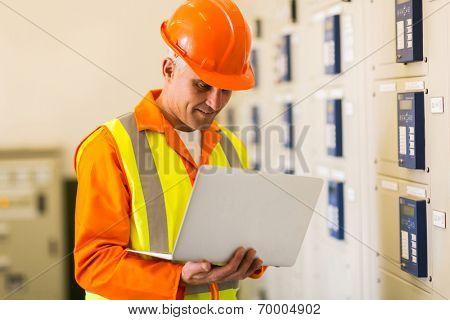 professional senior control room engineer using laptop