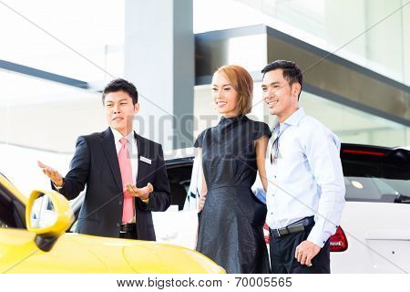 Asian couple buying car in auto dealership consulting the salesman