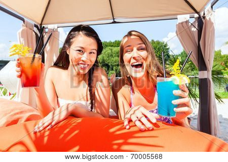 Girls in a beach bar drinking cocktails