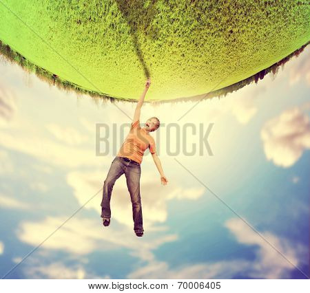 a woman doing a cartwheel on an upside down planet of green grass toned with a vintage retro instagram like filter