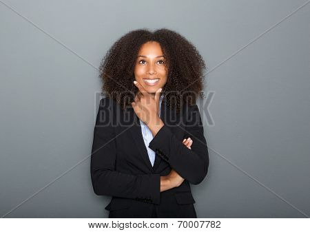 portrait of a confident young business woman thinking on gray background