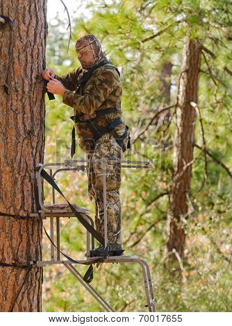 Bow hunter in a ladder style tree stand correctly attaching a fall arrest harness to a strap around the tree
