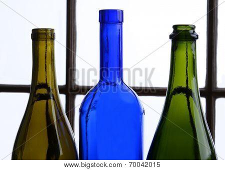 Empty wine bottle still life. Three wine bottles in front of a window.