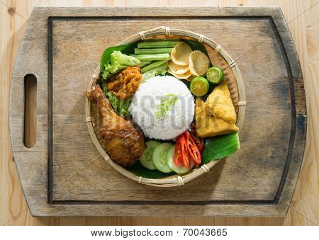 Delicious nasi ayam penyet with sambal belacan. Fried chicken rice with overhead view. Famous traditional Indonesian food.
