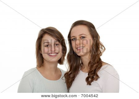 Two Young Modern Girls Smiling At You