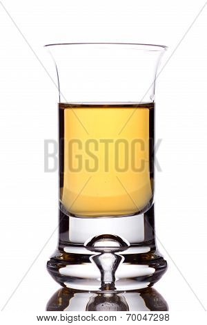 A Closeup Of A Shotglass Partially Full Of An Alcoholic Drink On White