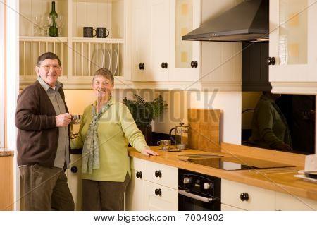 Senior Couple Portrait In Modern Designer Kitchen