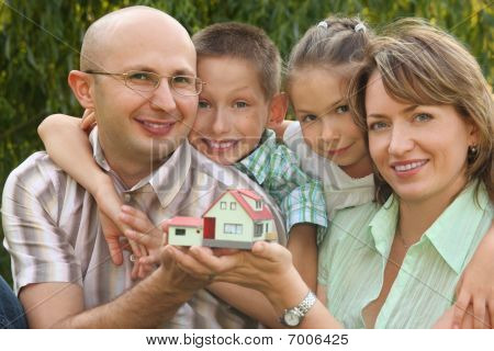 smiling family with two children is keeping wendy house in their hands and looking at camera