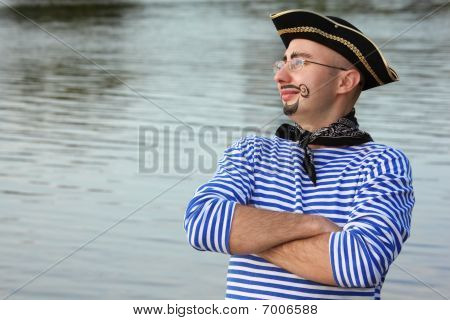 man with drawed beard and whiskers in pirate suit near pond is looking away
